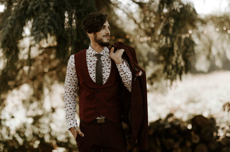 The groom was wearign a burgundy three-piece suit, a grey tie, a floral shirt and grey shoes