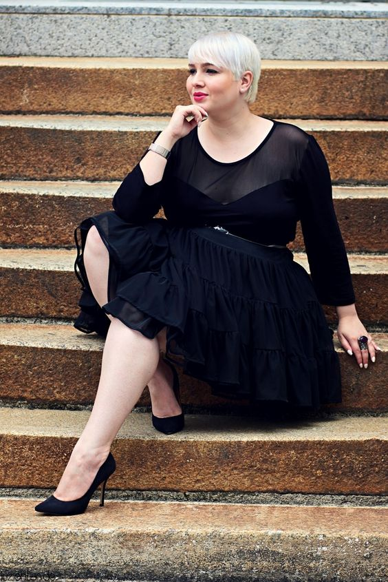 a chic black midi dress with an illusion strapless neckline, long sleeves, a ruffled skirt, black heels and an embellished sash