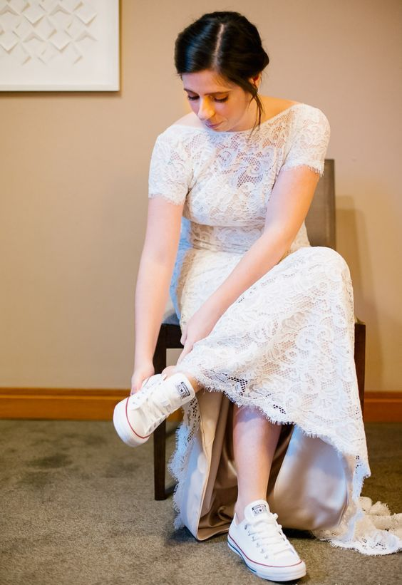 a lace fitting wedding dress with a high neckline and short sleeves, white Converse for a casual touch