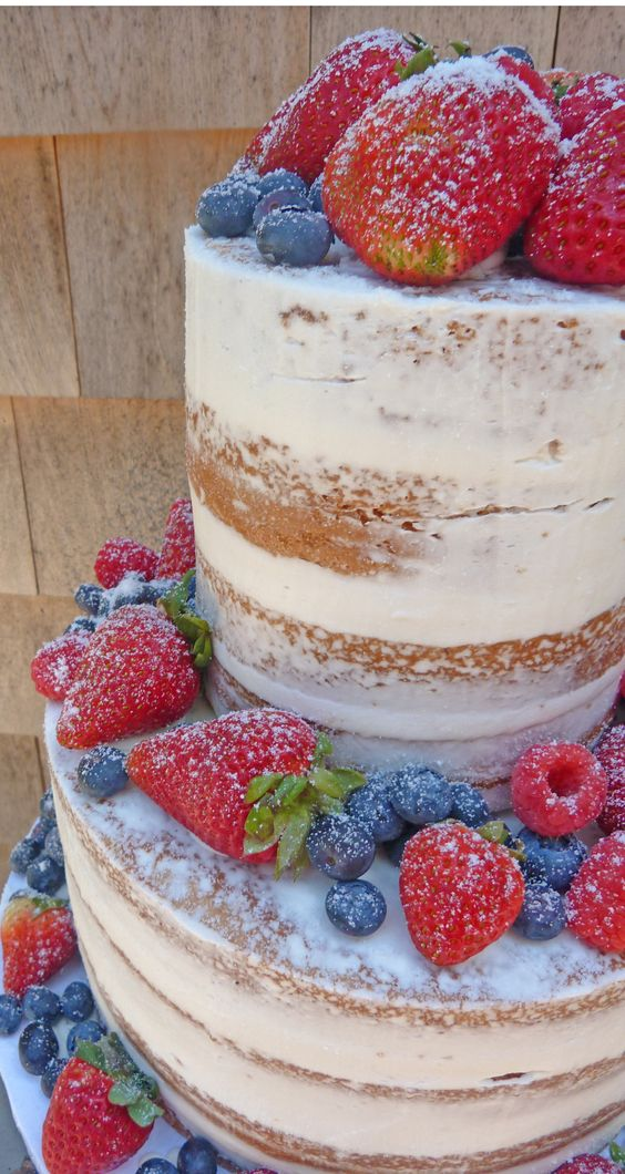 a vegan vanilla naked wedding cake with with fresh berries, a dustign of powdered sugar and vanilla frosting