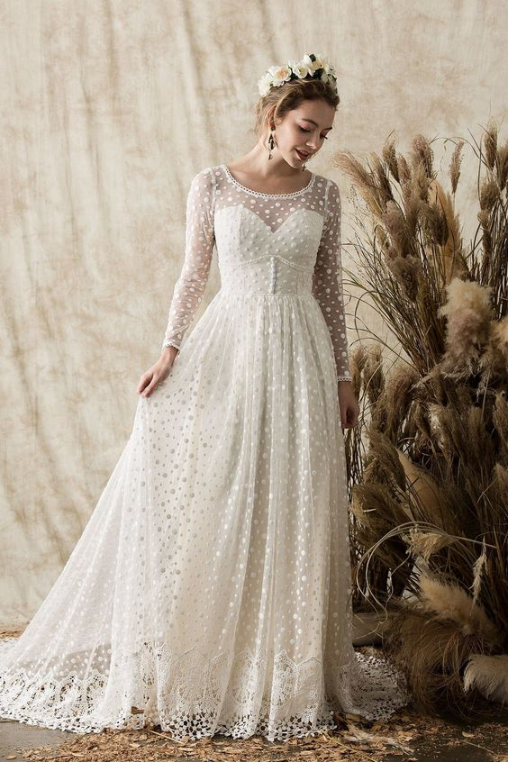a vintage-inspired polka dot wedding dress with an illusion strapless neckline, long sleeves and a lace trim