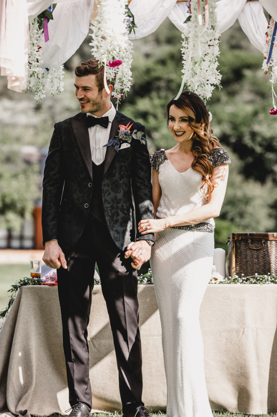 The groom was wearing a three-piece wedding suit with a green blazer with a damask pattern and a bow tie