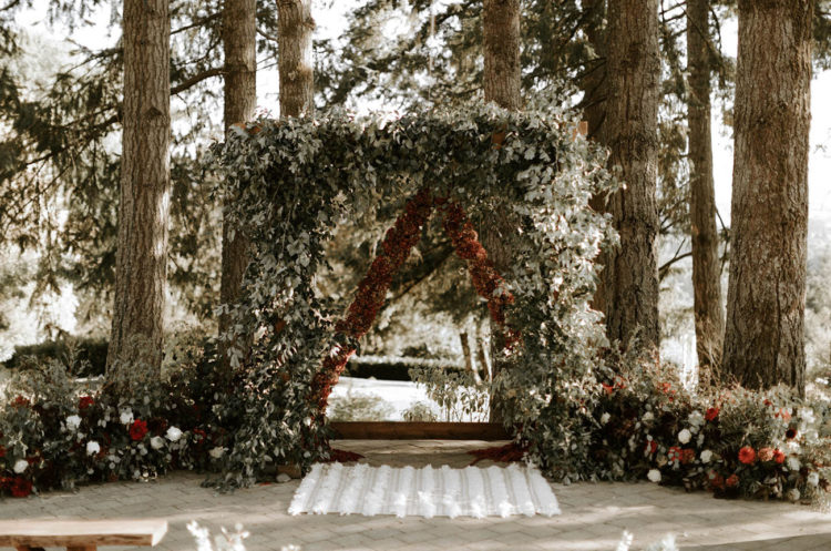 The wedding arch was of greenery, burgundy florals, and lush greenery all around added a woodsy pop