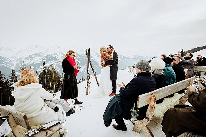 The wedding ceremony space was marked with a ski wedding arch decorated with greenery and there were benches covered with faux sheepskins