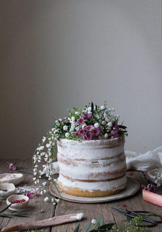 a vegan rhubarb naked wedding cake topped with white and pink flowers going down