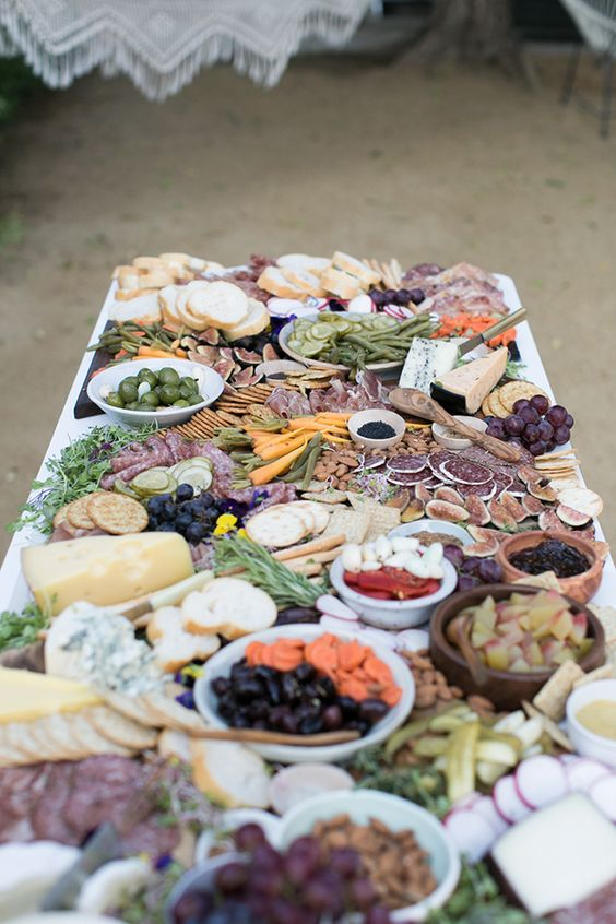 a charcuterie table with olives, cheese, figs, salami, greenery and crackers served