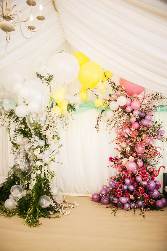 a dazzling wedding arch made with greenery, white and sheer balloons on one side and colorful blooms and balloons on the other