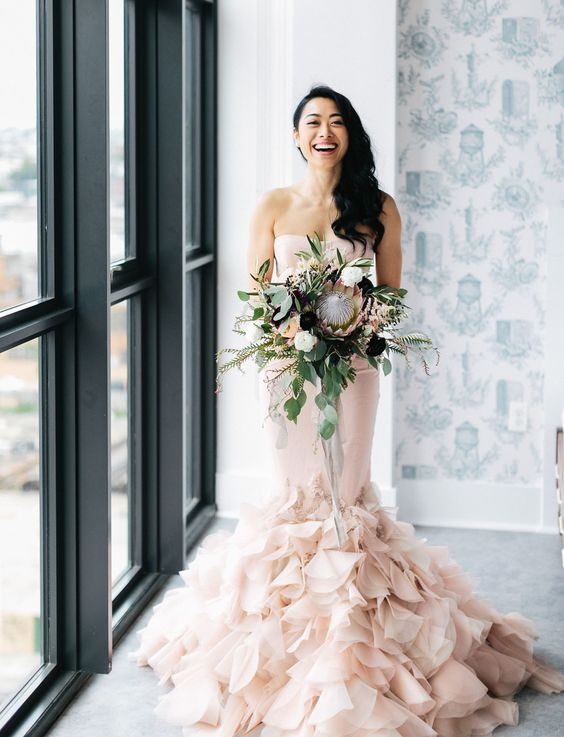 a gorgeous blush mermaid strapless wedding dress with a ruffled tail