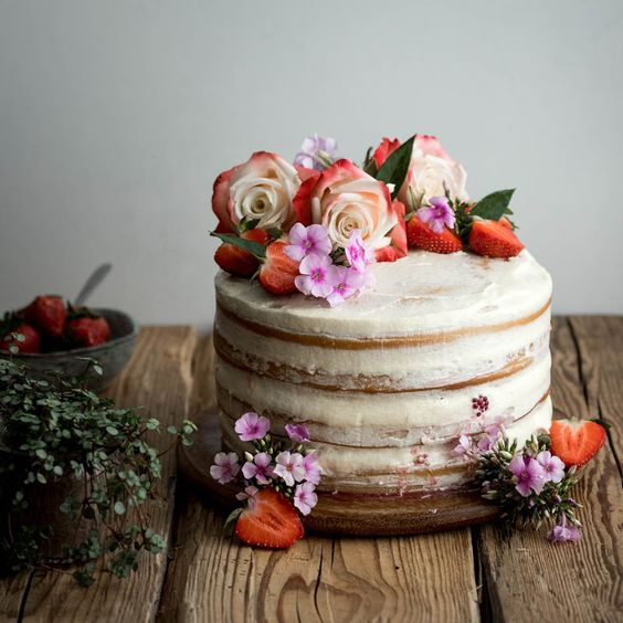 a vegan vanilla and berry layer cake with almond milk and fresh raspberries topped with blooms