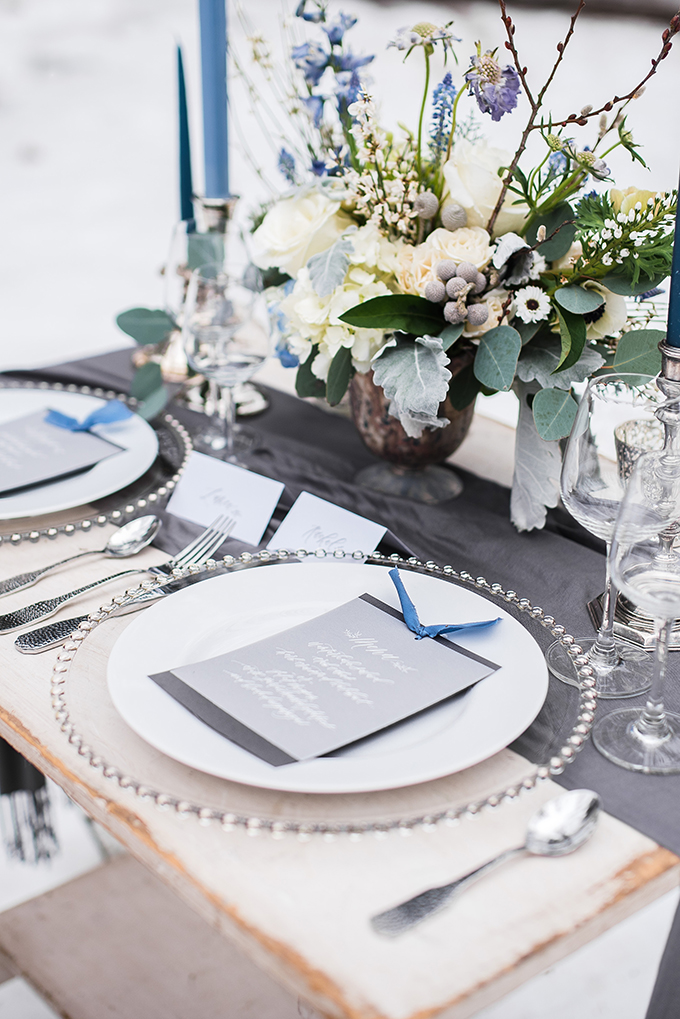 Metallic chargers, silver cutlery, blue candles and grey menus create a chic winter tablescape