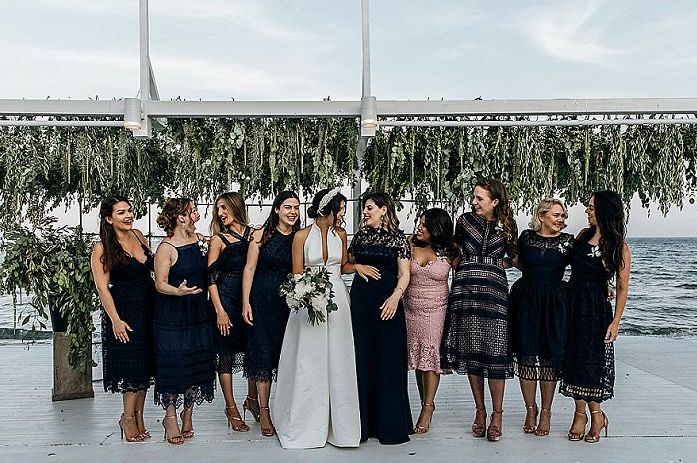The bridesmaids were wearing mismatching black midi gowns, and the maid of honor was rocking blush