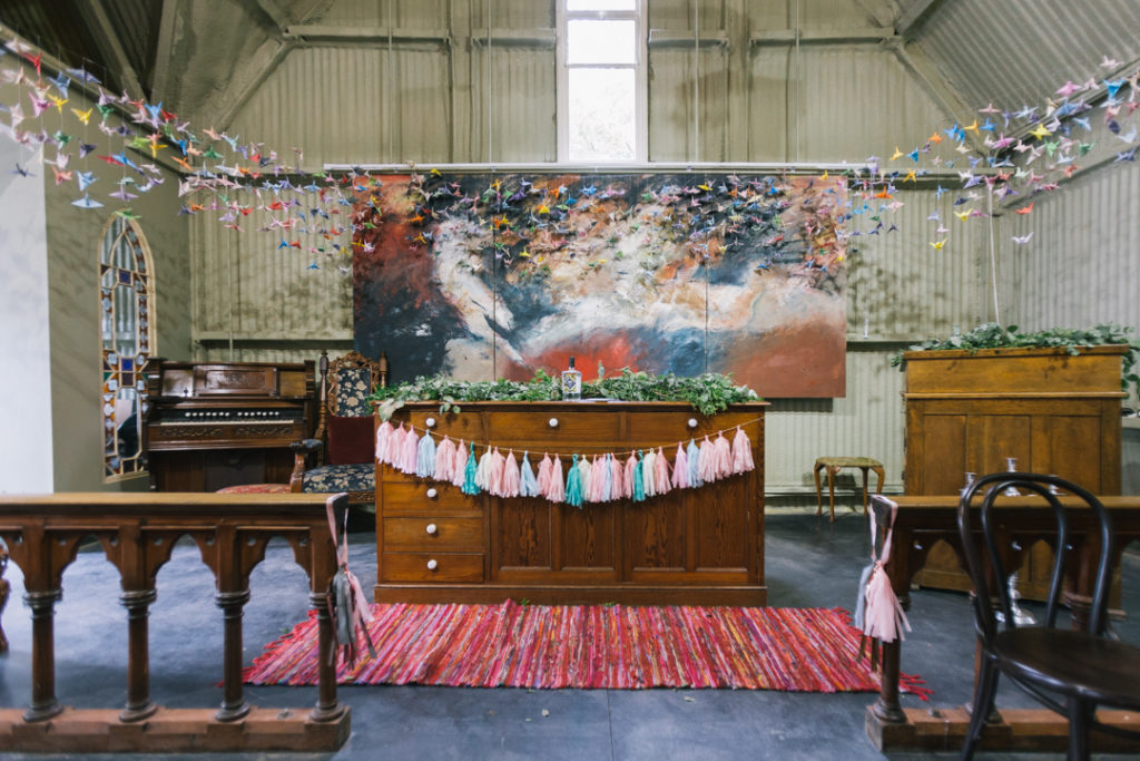 The ceremony space was done with a watercolor artwork, colorful tassels and lots of colorful paper cranes