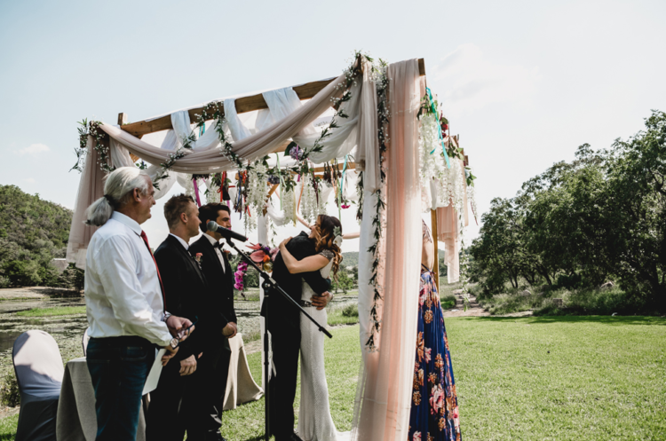The wedding arch was made of wood, with some blusha nd white fabric and lush blooms hanging down