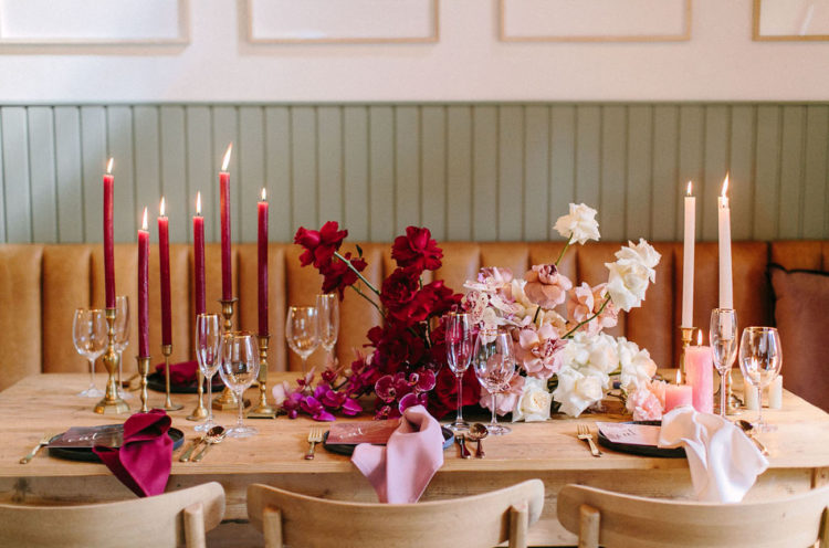 The wedding tablescape is striking an ombre floral centerpiece from hot red and fuchsia to cream