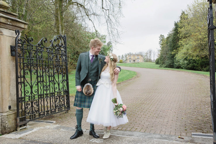 a 50s inspired polka dot tea-length wedding dress with an illusion neckline, a large bow sash and neutral sneakers
