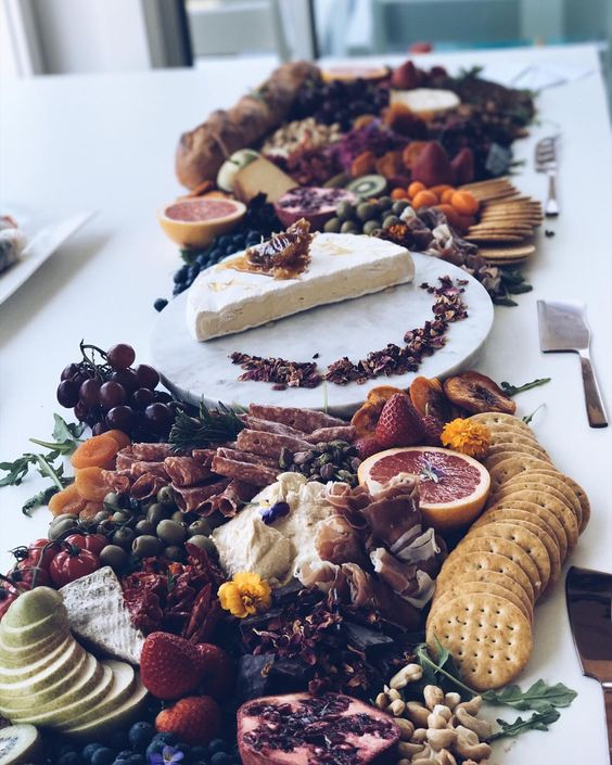 a chic charcuterie table with different types of cheese, salami, fruts, crackers and berries