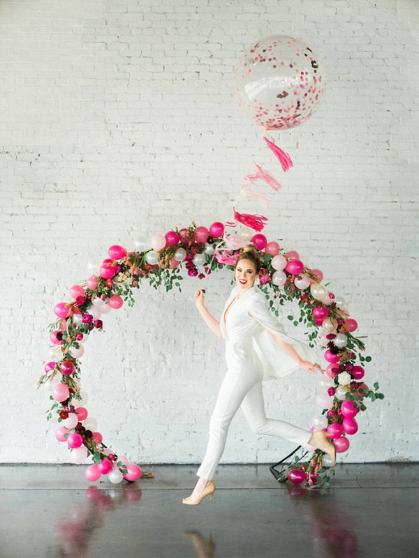 a cute oversized wreath balloon, greenery and floral wedding arch in hot pink and blush for a modenr glam wedding