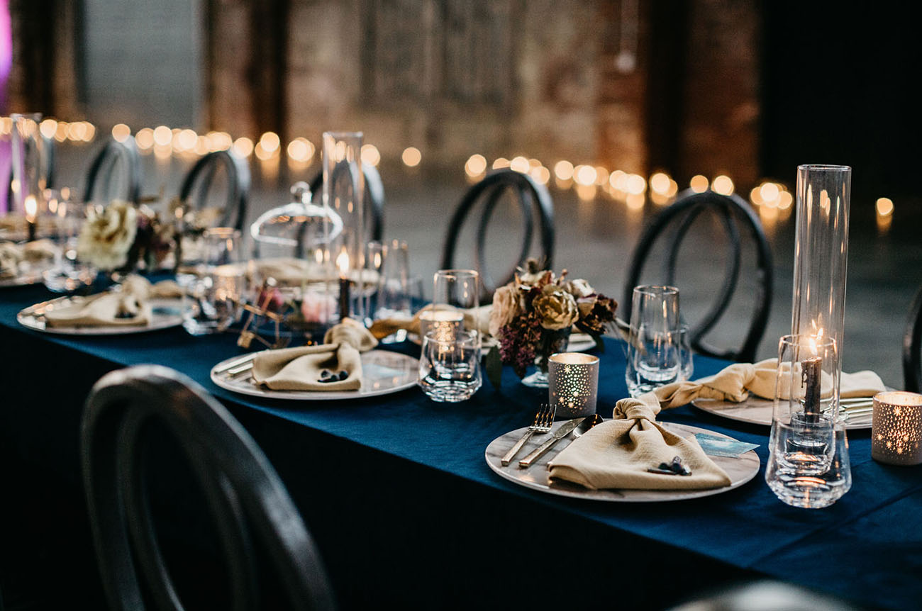 The wedding reception tables were done with navy tablecloths and metallic touches plus dried and moody blooms
