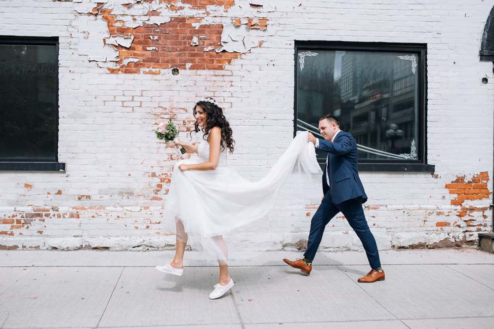 a romantic lace embellished wedding gown with a train and white sneakers for a modern bridal outfit