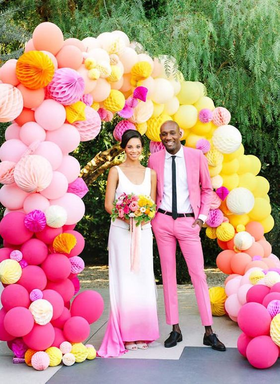 a super colorful wedding arch composed of pink, blush, yellow and orange balloons and paper balls