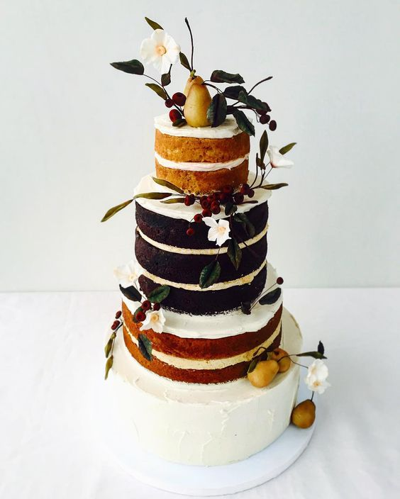 a vegan gluten-free naked wedding cake topped with white blooms, greenery and pears