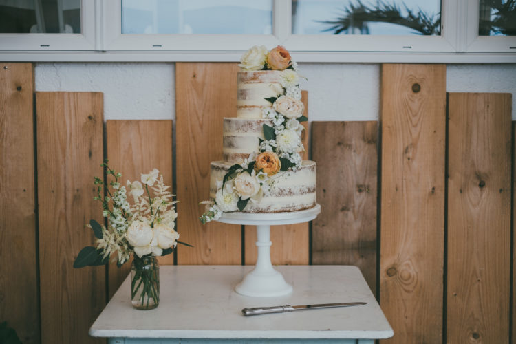 The naked wedding cake was decorated with neutral blooms and greenery