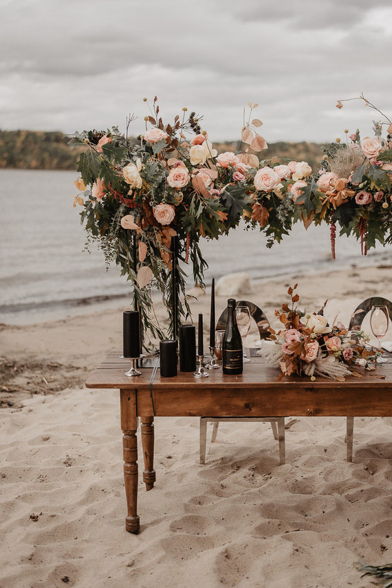 The second reception took place on a sandy beach, with a lush overhead floral decoration and black candles