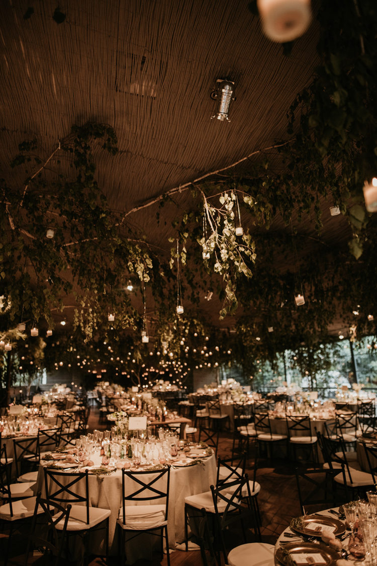 The wedding venue was decorated with lush greenery and branches and hanging lights