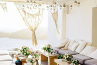 09 What a beautiful wedding lounge with little tables and upholstered benches with sea views