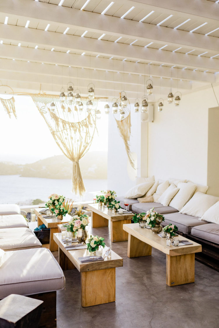 What a beautiful wedding lounge with little tables and upholstered benches with sea views