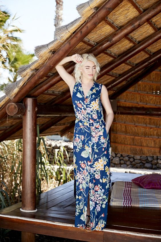 a bright navy maxi dress with a floral print, a front slit, a V-neckline and no sleeves brings a vintage feel