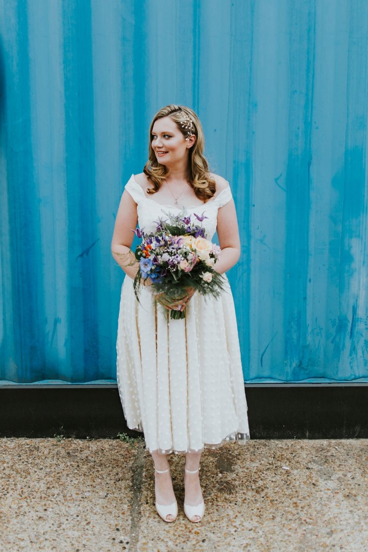 a polka dot off the shoulder tea-length wedding dress with neutral ankle strap shoes and a statement hairpiece