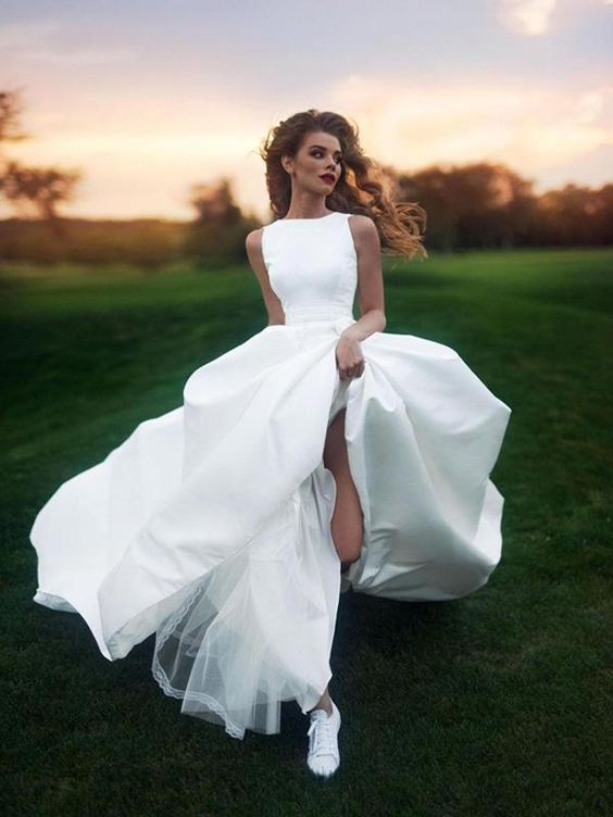 a super modern bridal look with a plain A-line wedding gown with no sleeves and white sneakers