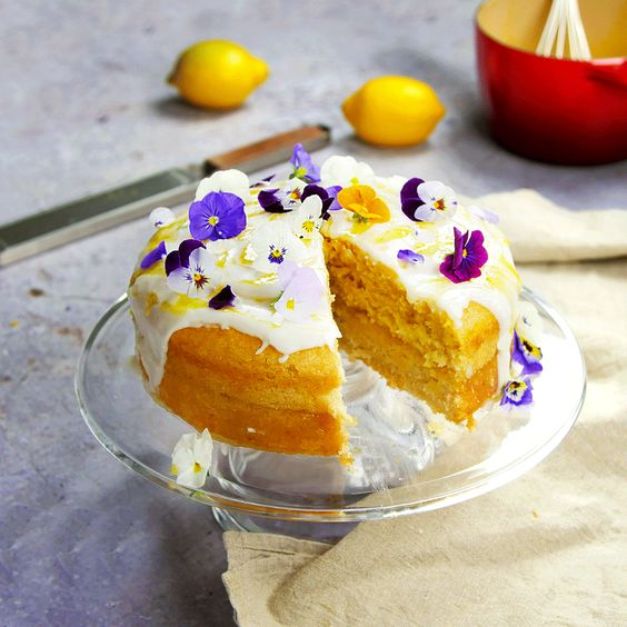 a vegan lemon drizzle wedding cake topped with fresh blooms is dairy-free and egg-free