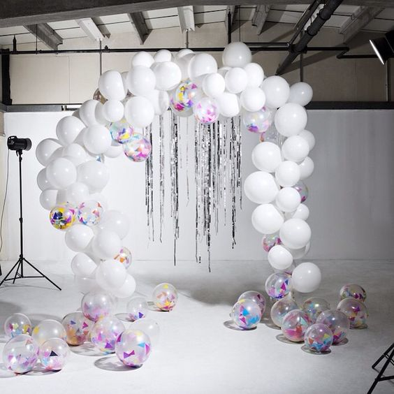 a white balloon wedding arch with sheer ones filled with colored paper and silver rain hanging down