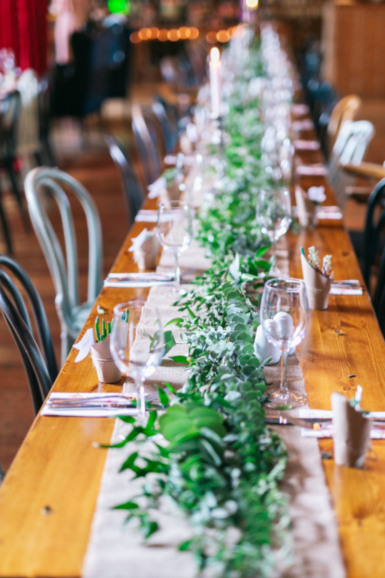 The wedding reception tables were done with fresh greenery and succulents and neutral textiles