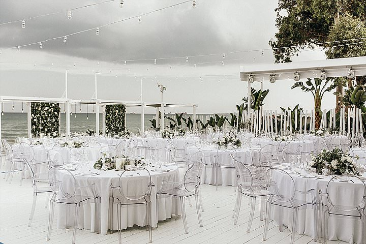The wedding reception was also done in white, with acrylic chairs and greenery and white blooms on the tables