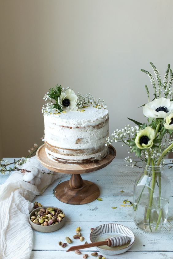 a vegan matcha pistachio tres leches wedding cake with fresh blooms on top