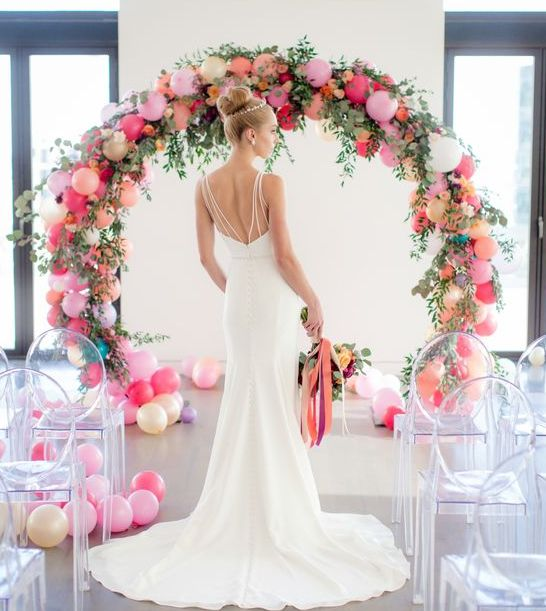 a whimsy wedding arch of colorful balloons, greenery and flowers and acrylic chairs to accent the arch