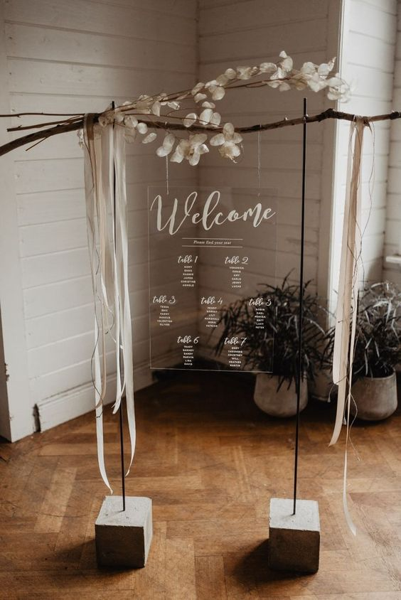 an acrylic seating chart decorated with ribbons and lunaria branches looks very chic and catchy