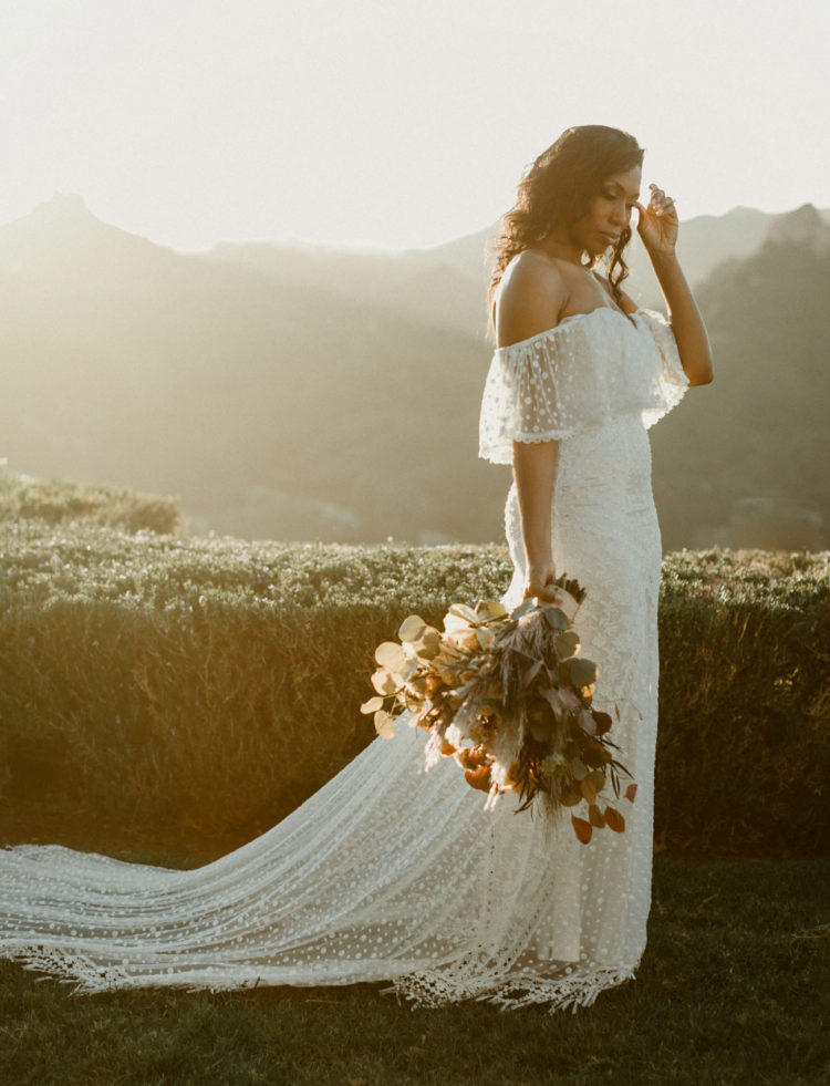 a fantastic lace off the shoulder wedding dress with a long train and fringe looks super romantic