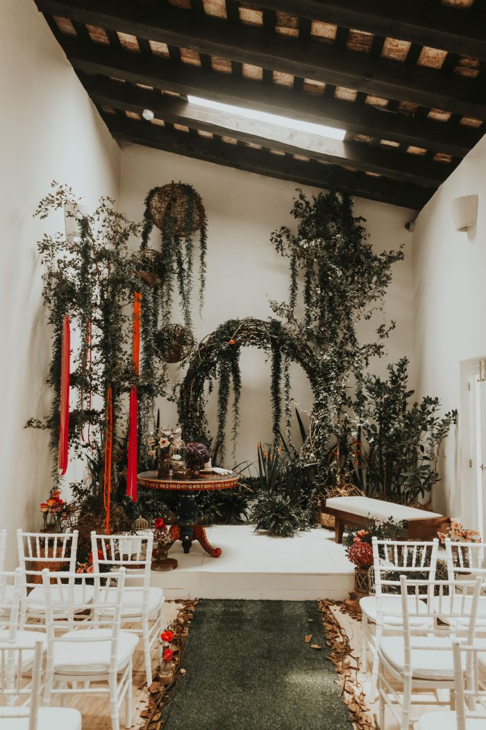 a lush wedding greenery backdrop done with lots of potted plants, hanging pots and a large wreath arch