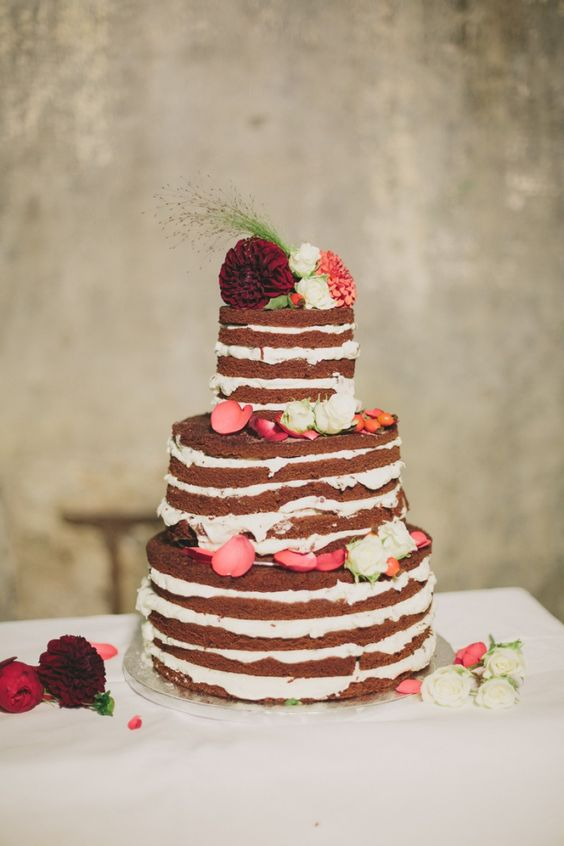 a vegan red velvet naked wedding cake with vegan cream topped with fresh blooms and petals