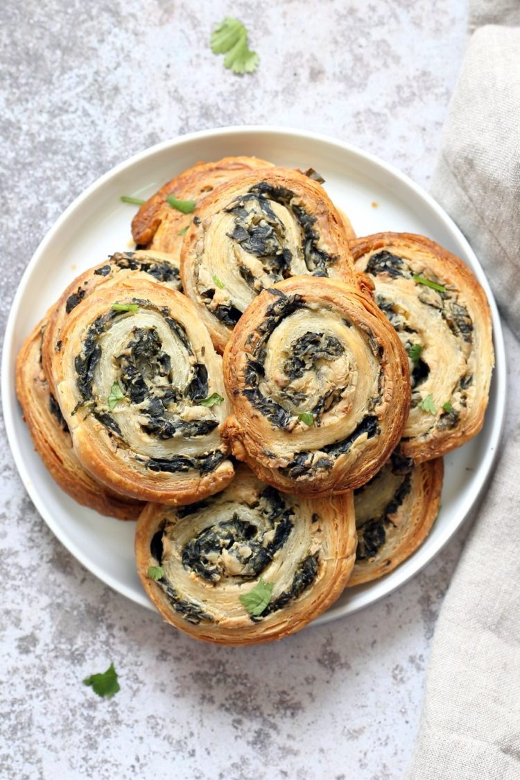 vegan spinach cream cheese pinwheels are puff pastry, rolled, sliced and baked to make a great snack