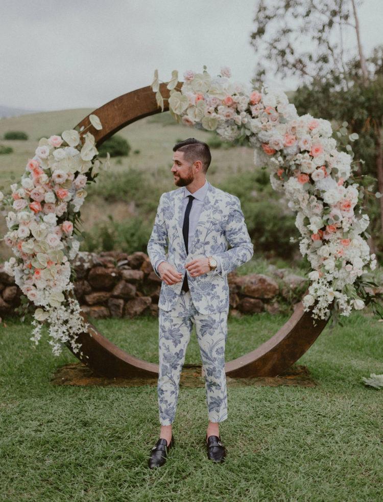 a blue floral print suit, a white shirt, a black tie and black shoes with no socks is a very daring idea