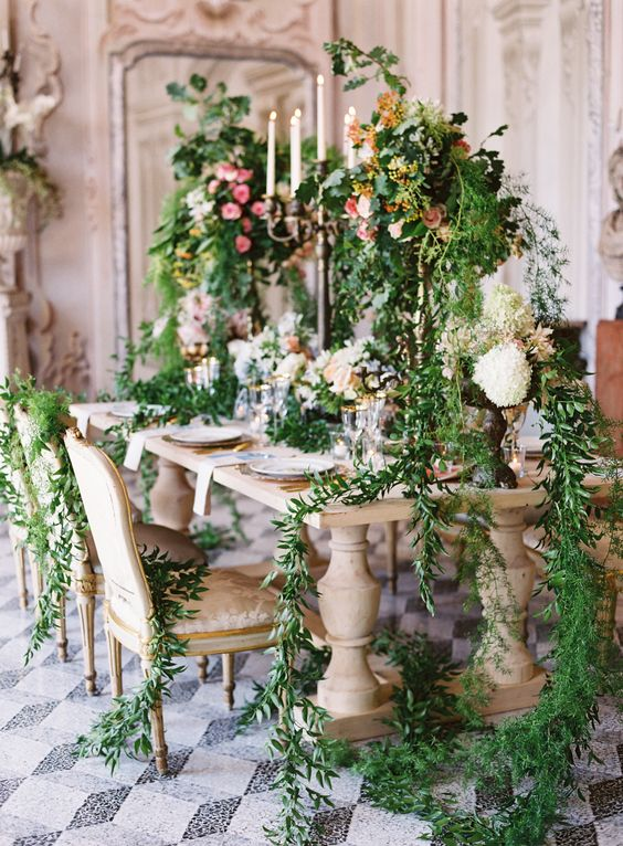 a super lush floral table setting with lots of cascading greenery, centerpieces and even chairs decorated with greenery