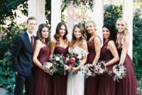 13 girls wearing burgundy maxi dresses and a guy rocking a black suit with a burgundy tie