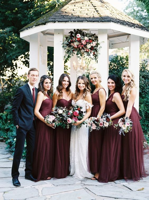 girls wearing burgundy maxi dresses and a guy rocking a black suit with a burgundy tie