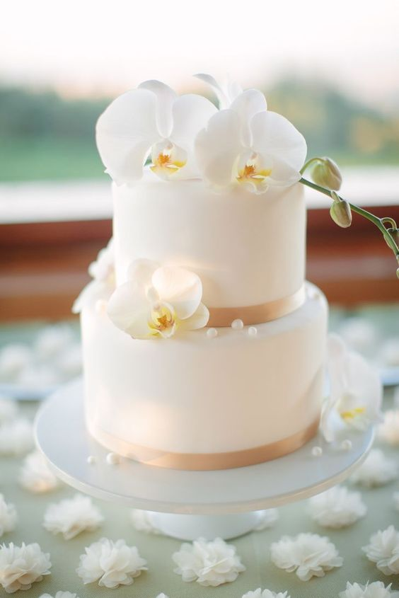 a classic wedding cake topped with fresh orchids and edible pearls is always a chic idea