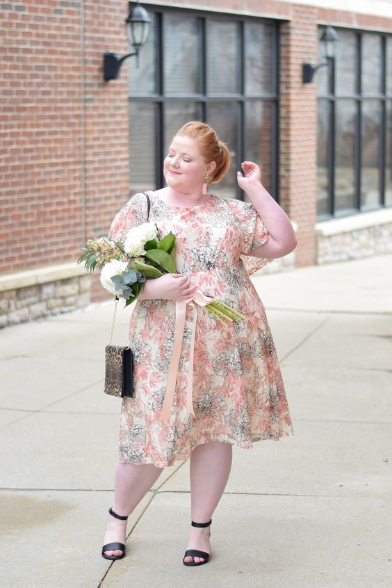 a stylish floral midi dress in muted shades, with short sleeves, black shoes and a leopard bag
